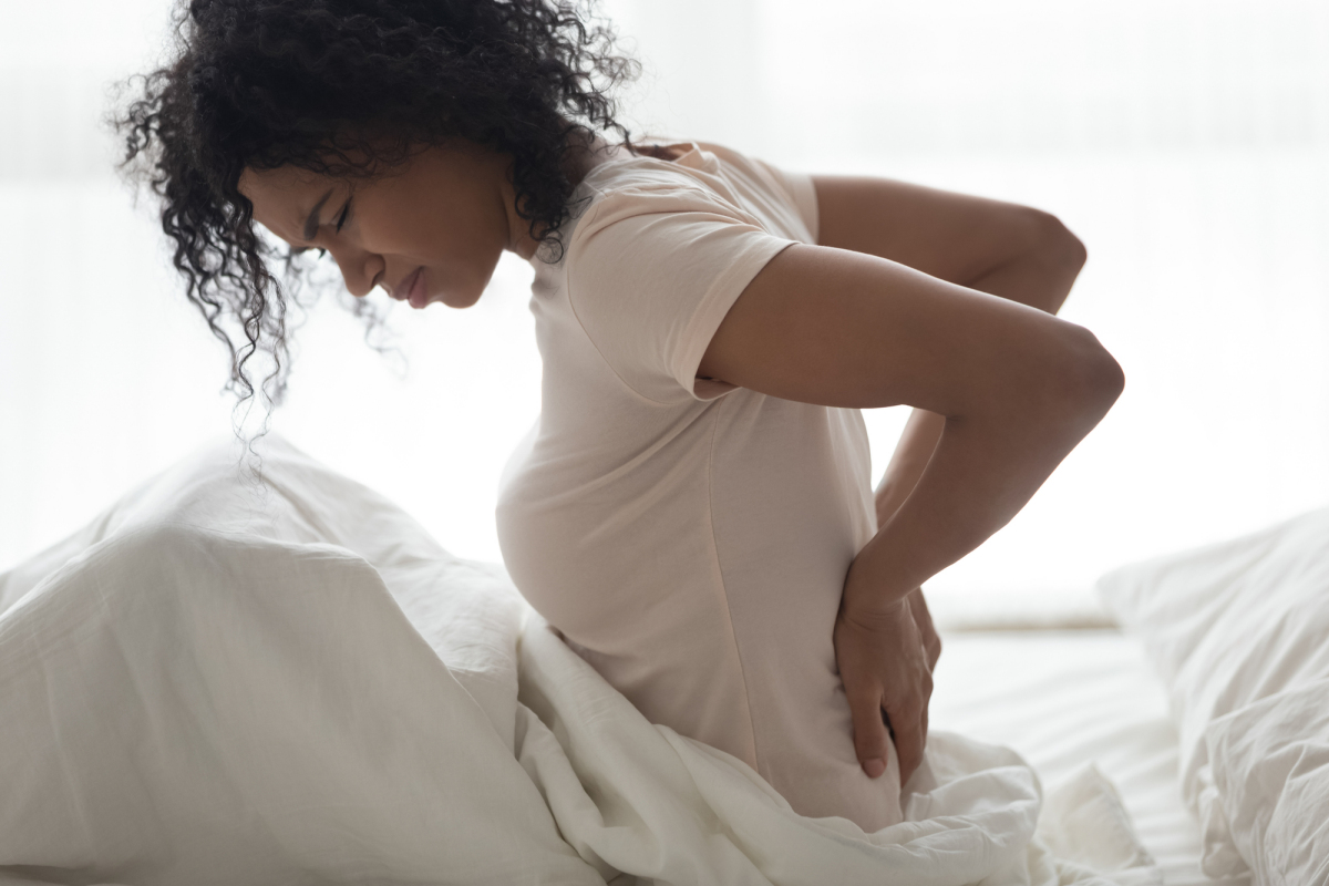 Young woman with back pain in bed